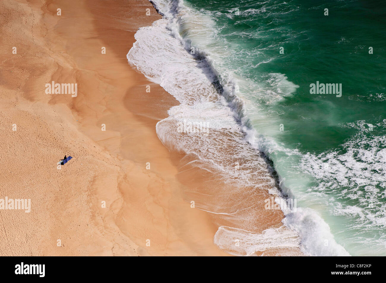 Nazaré beach, a solitary sunbather watches large waves crash onto the shore, from above at Sitio - Stock Image