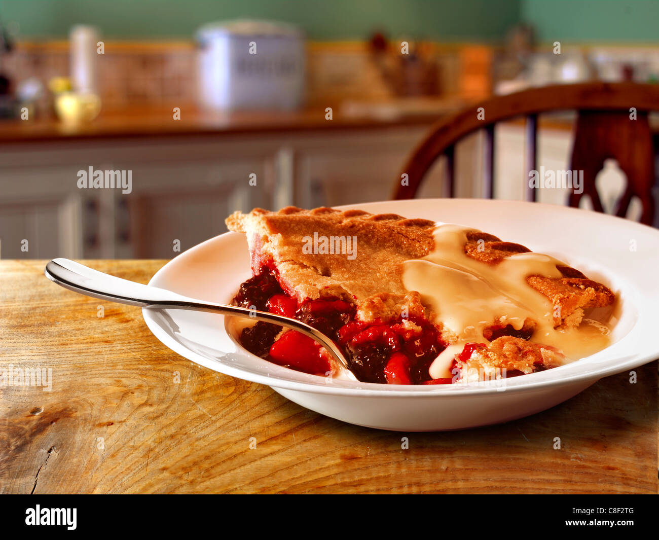 Traditional British fruit pie and custard pudding served hot in a bowl on a table in a traditional kitchen setting - Stock Image