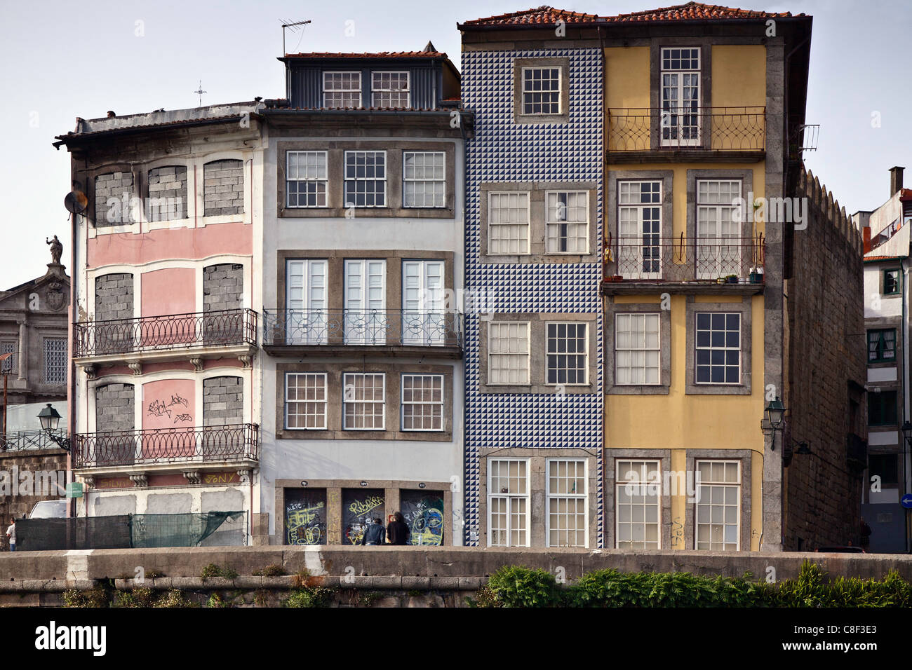 Porto, traditional buildings by the River Douro with two people and grafitti - Stock Image