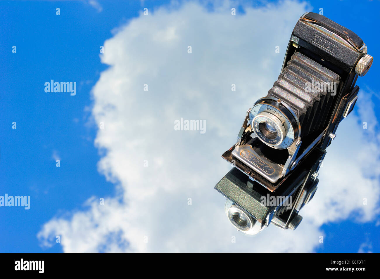 Old bellows camera reflected against the sky - Stock Image