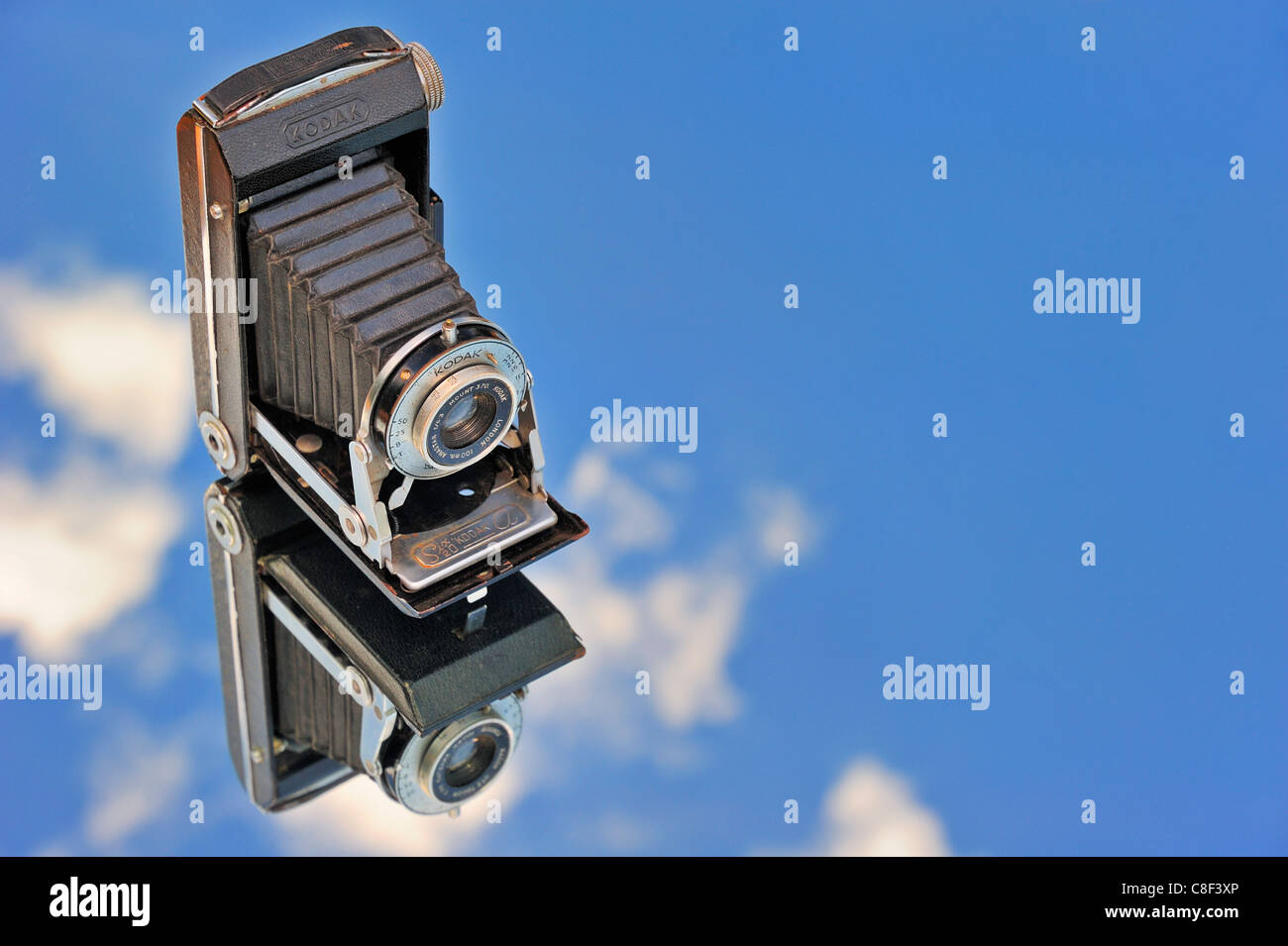 An old bellows camera reflected against the sky. Space for text in the sky. - Stock Image