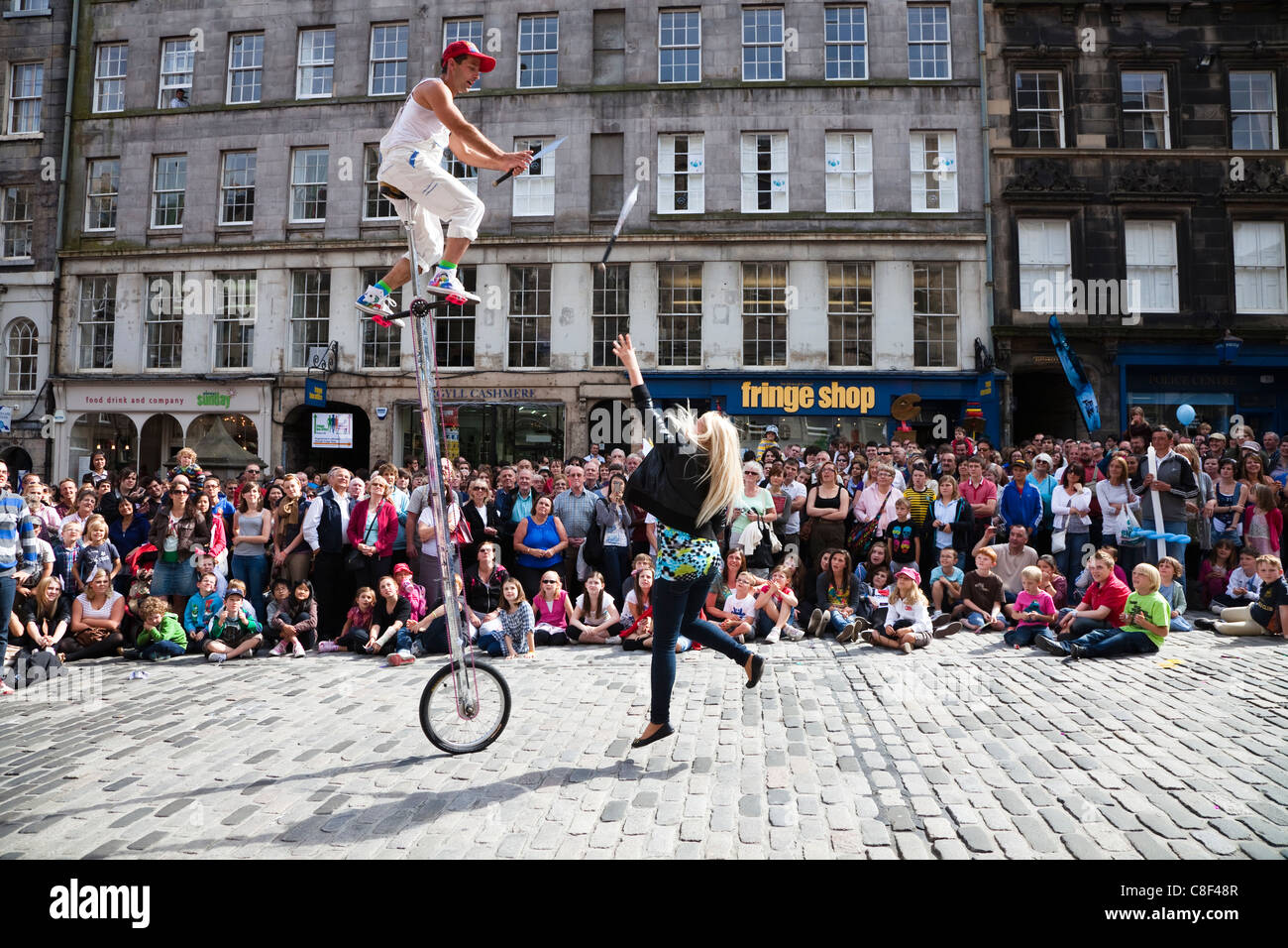 Juggler at Edinburgh Festival on a unicycle getting a woman to throw knives for him to catch - Stock Image