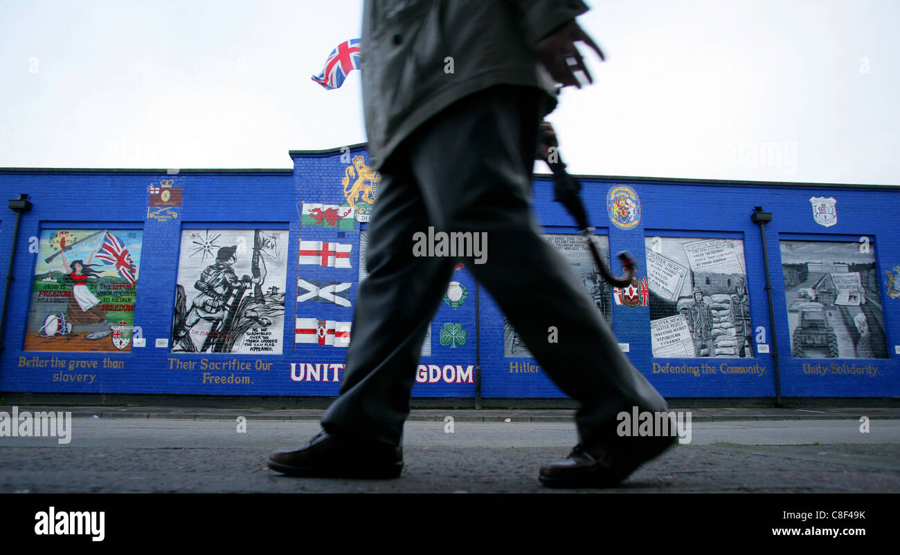 A man walks pass a Loyalist mural in the streetsof the Sandy Row area in Belfast, Northern Ireland - Stock Image