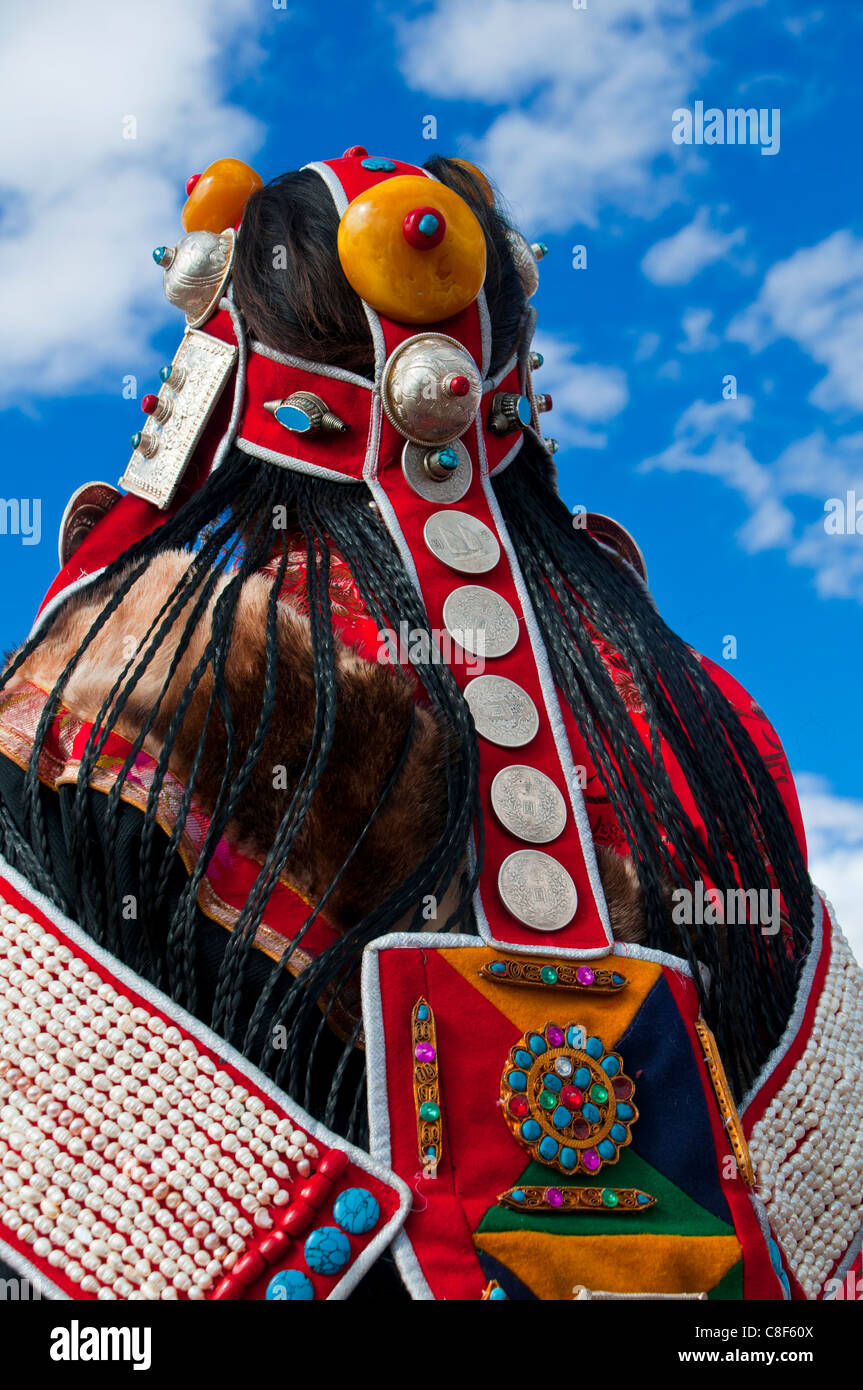 Back view of Tibetan woman's traditional headdress at festival, Gerze, Tibet, China - Stock Image