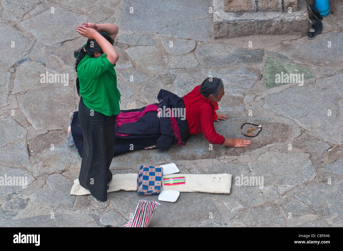Pilgrims praying before the Jokhang Temple in Lhasa, Tibet, China - Stock Image
