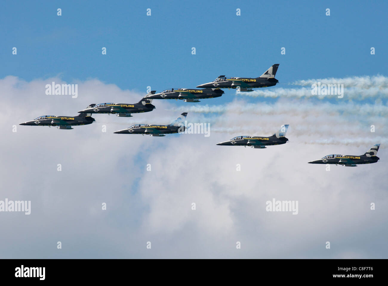 L-39C Albatros aircrafts from the Breitling Jet Team  flying in formation and leaving smoke trails in the sky during - Stock Image