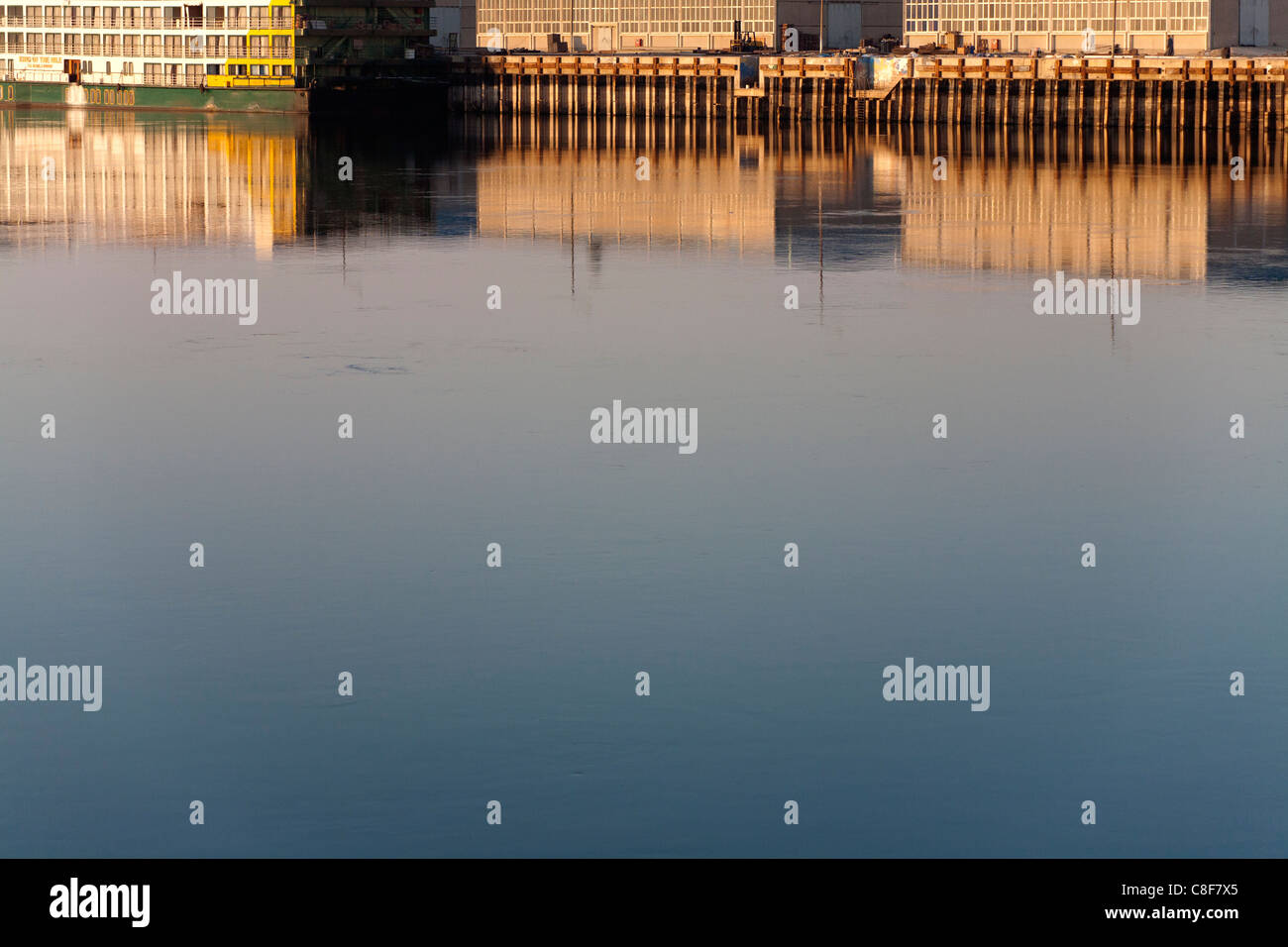 Reflections in golden water in early morning light of redundant cruise ships moored near industrial buildings on - Stock Image