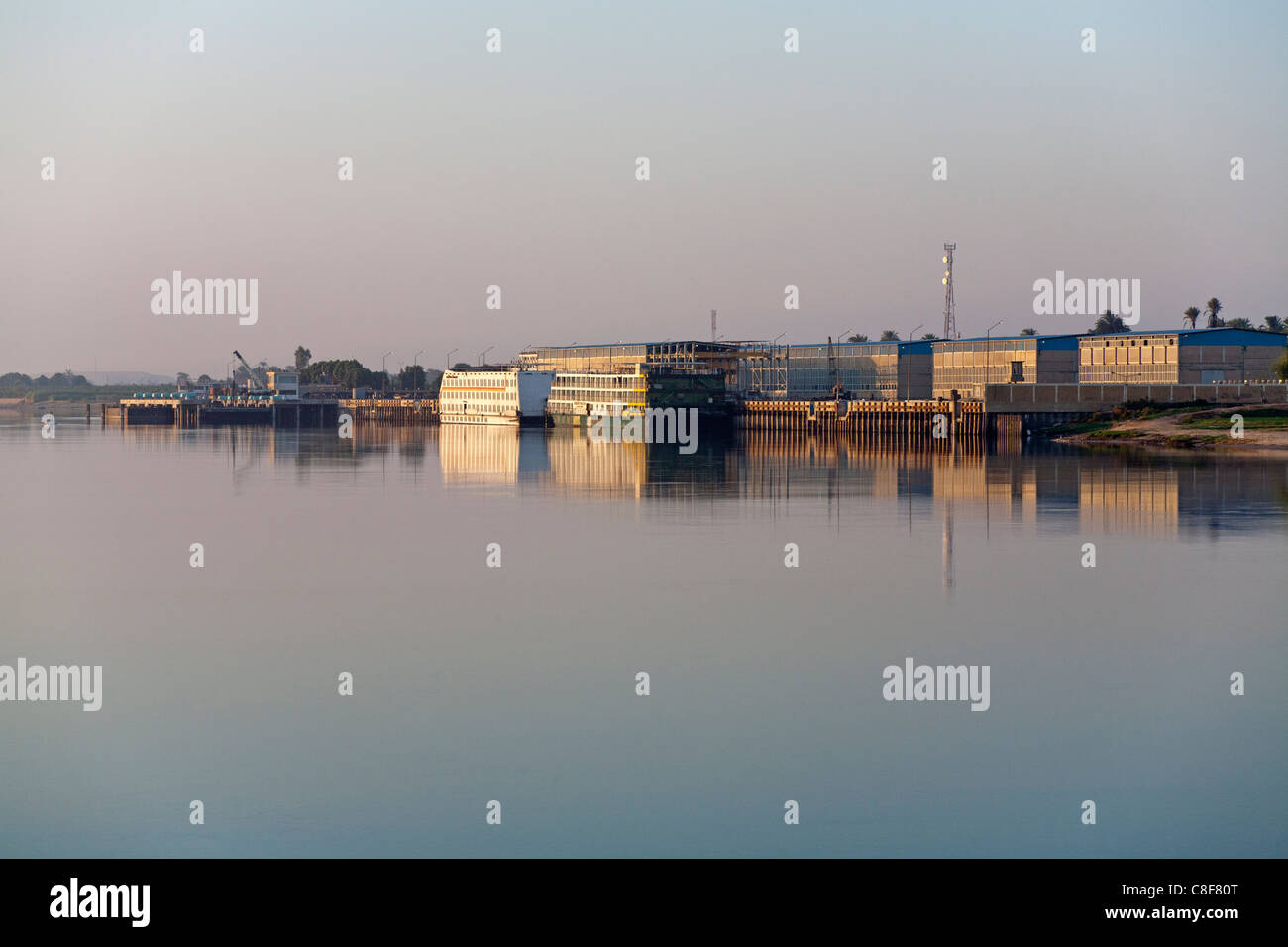 Redundant cruise ships moored near industrial buildings on the Nile reflecting in the golden water in early morning - Stock Image