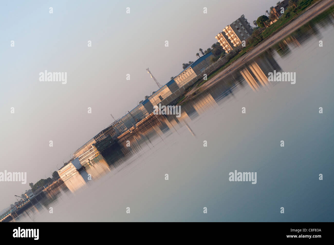 Redundant cruise ships moored near industrial buildings on the Nile reflecting in the golden water, diagonally placed - Stock Image