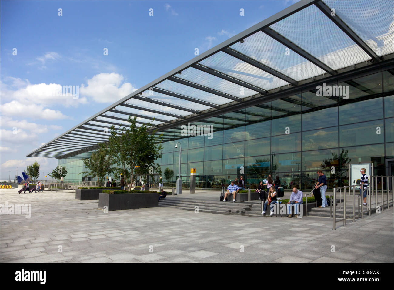 Passengers wait outside Terminal 4, Heathrow Airport, London, England, United Kingdom - Stock Image