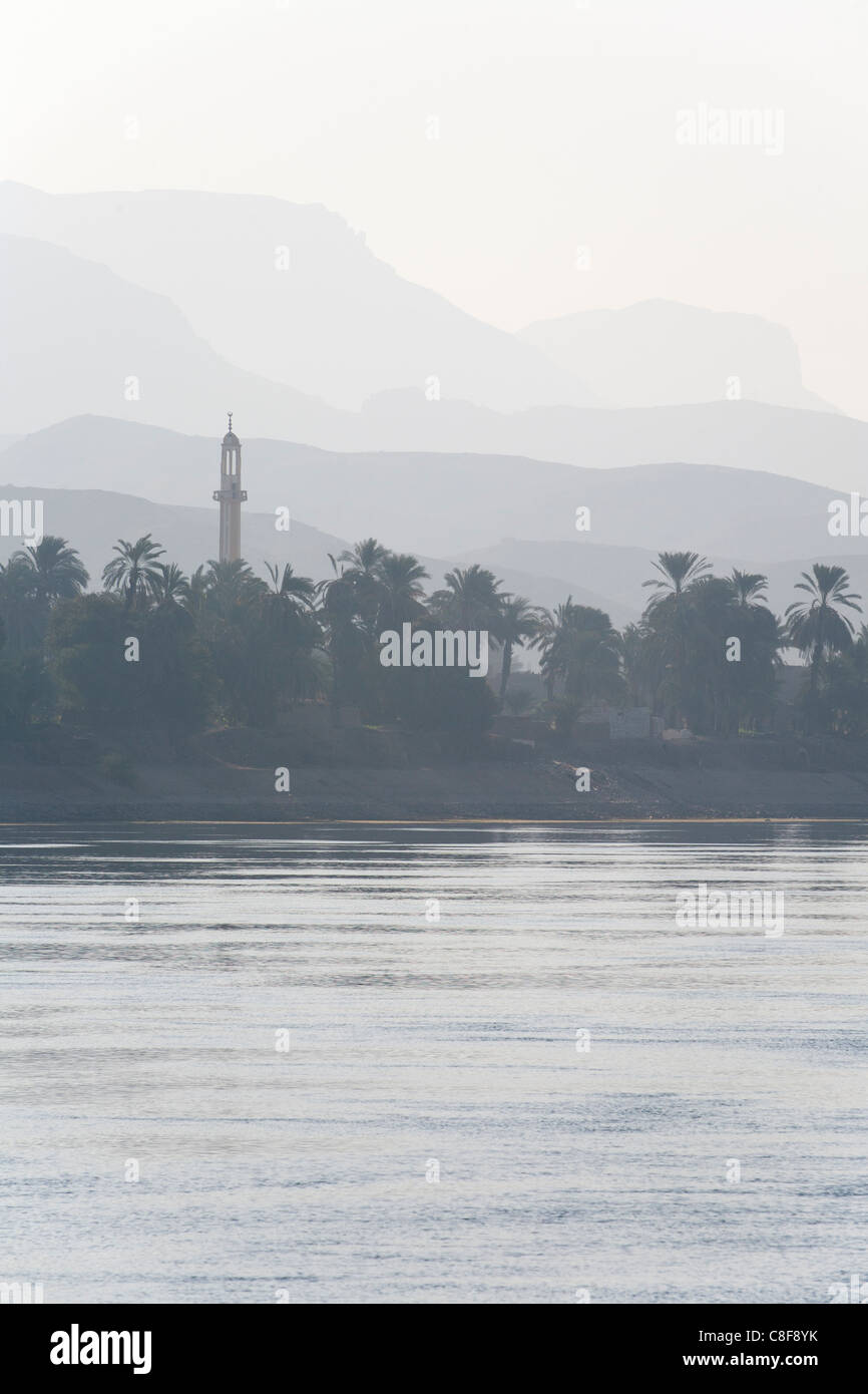 A section of Nile river bank with heavy mist creating muted colour layers, water trees, palms and mosque minaret, - Stock Image