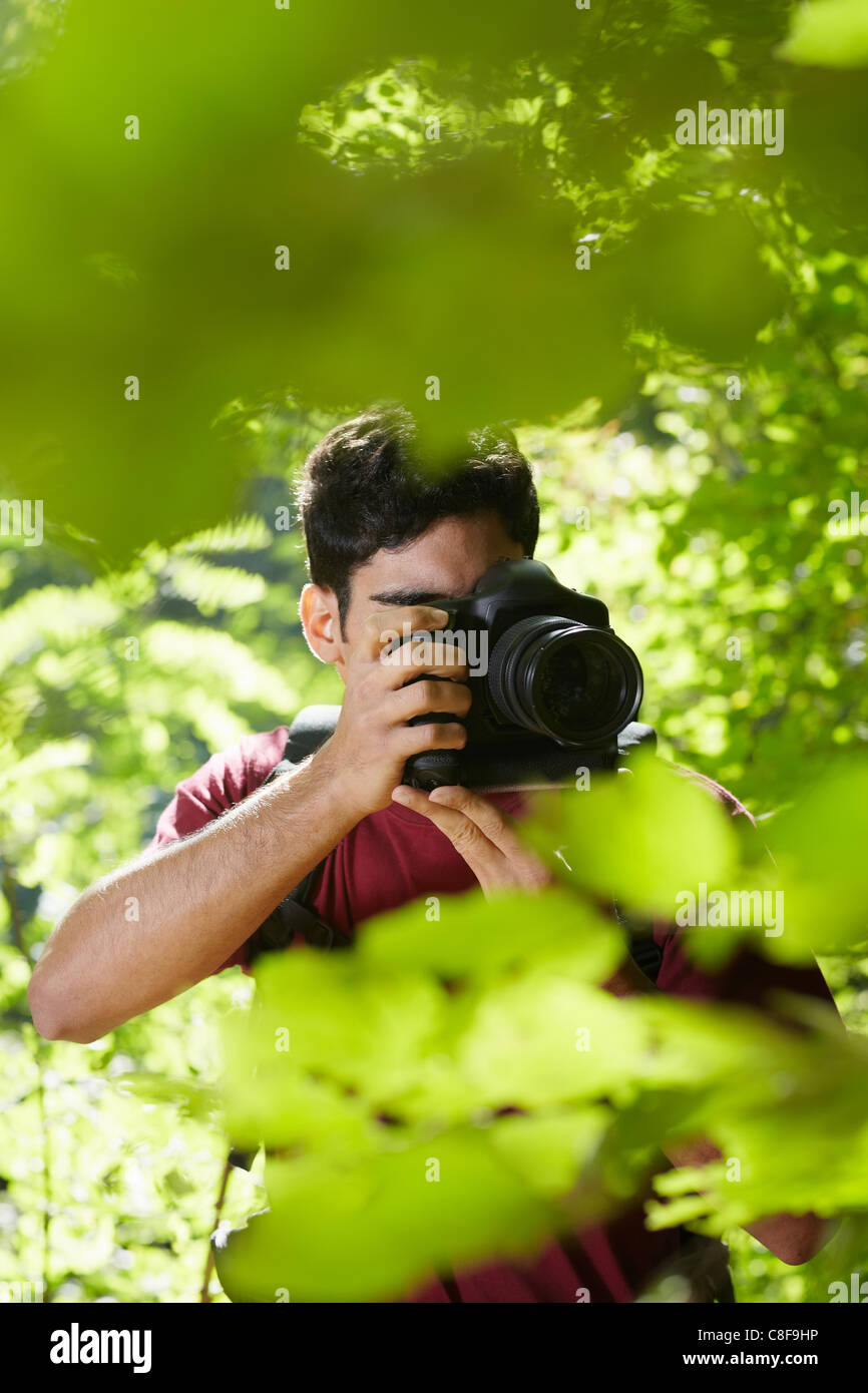 young hispanic man trekking among trees and taking pictures with dslr camera. Vertical shape, front view, copy space - Stock Image