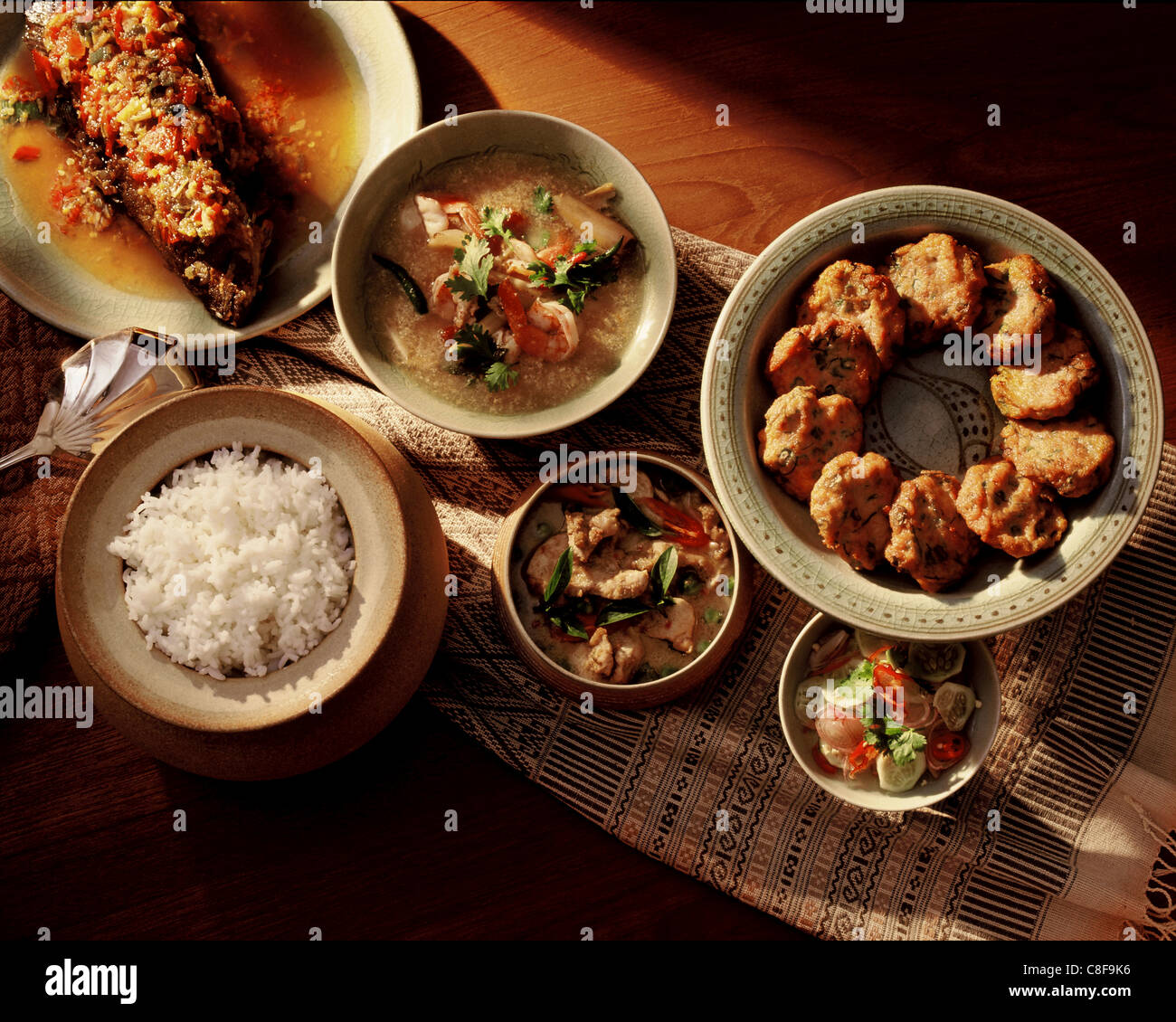 Thai meal,thom yam soup, weet and sour fish, fish patties, a curry dish and rice, Thailand - Stock Image