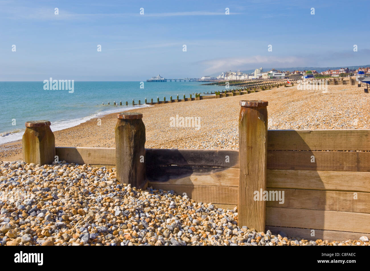 Pebble beach and groynes, Eastbourne Pier in the distance, Eastbourne, East Sussex, England, United Kingdom - Stock Image