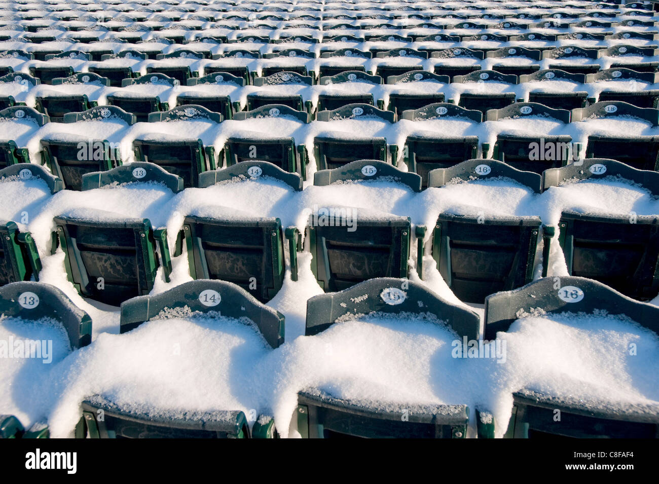 Snow covered seats in a baseball stadium. - Stock Image