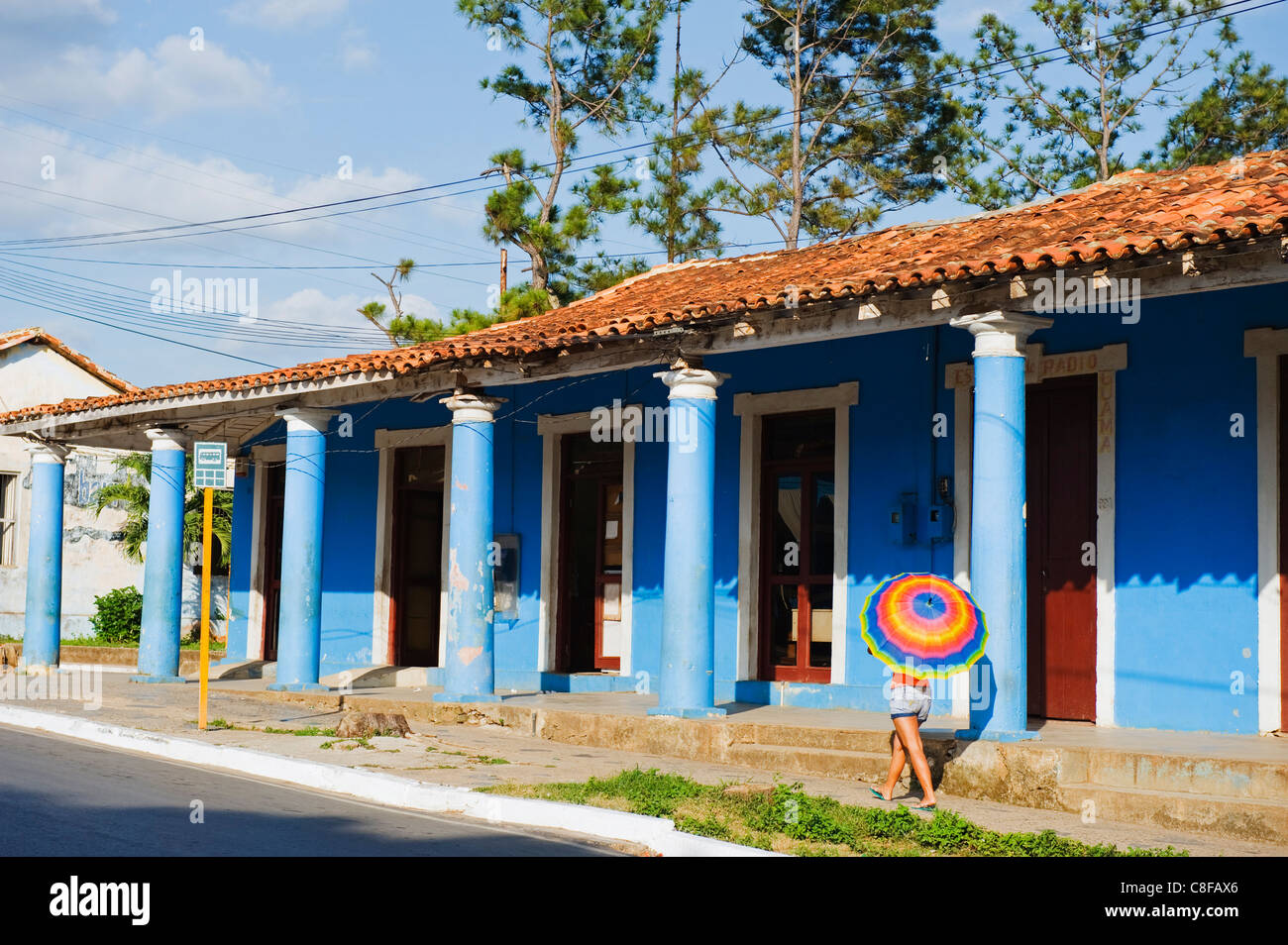 Woman with parasol walking past a colourful building, UNESCO World Heritage Site, Vinales Valley, Cuba, West Indies, - Stock Image