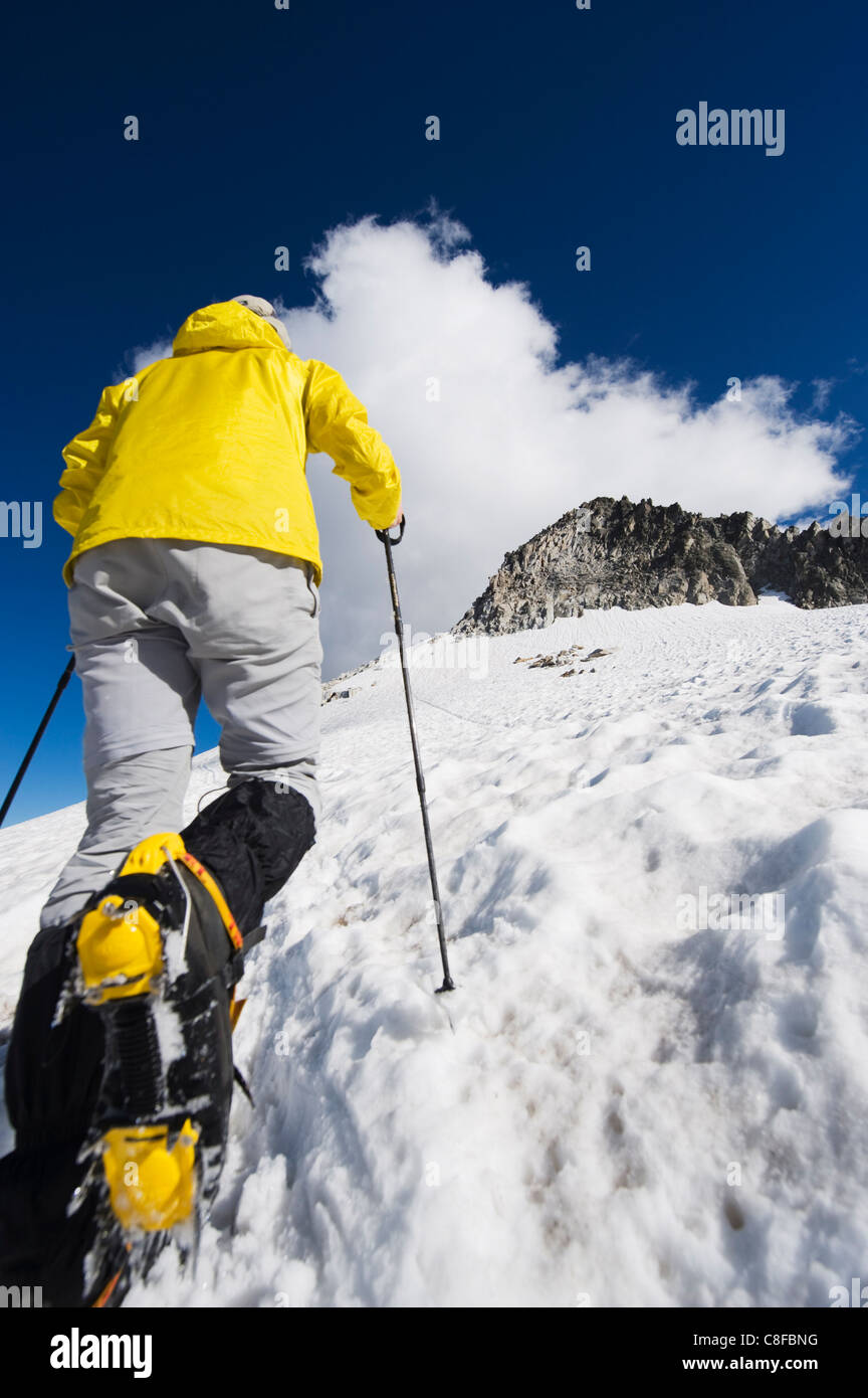 A climber walking up a snowfield, Pico de Aneto, the highest peak in the Pyrenees, Spain - Stock Image