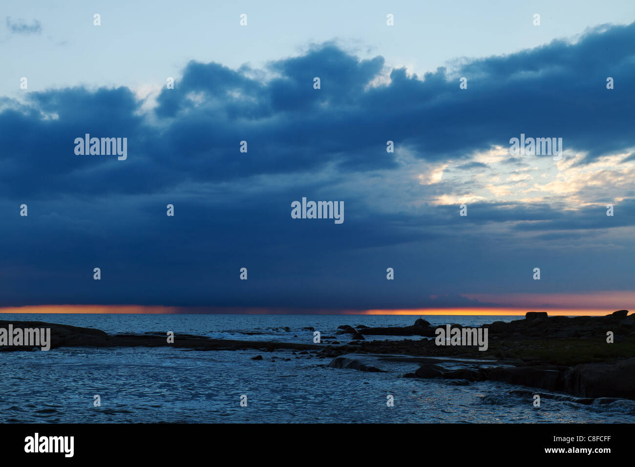 Rain cloud with rain out in the sea by sunset, outside Apelviken, Varberg, on the Swedish west coast. - Stock Image