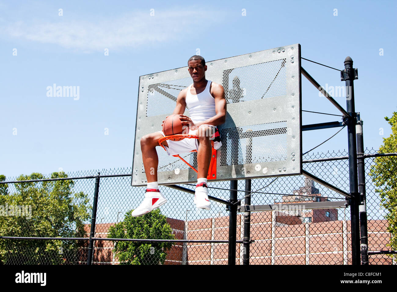 Basketball player sitting in hoop - Stock Image