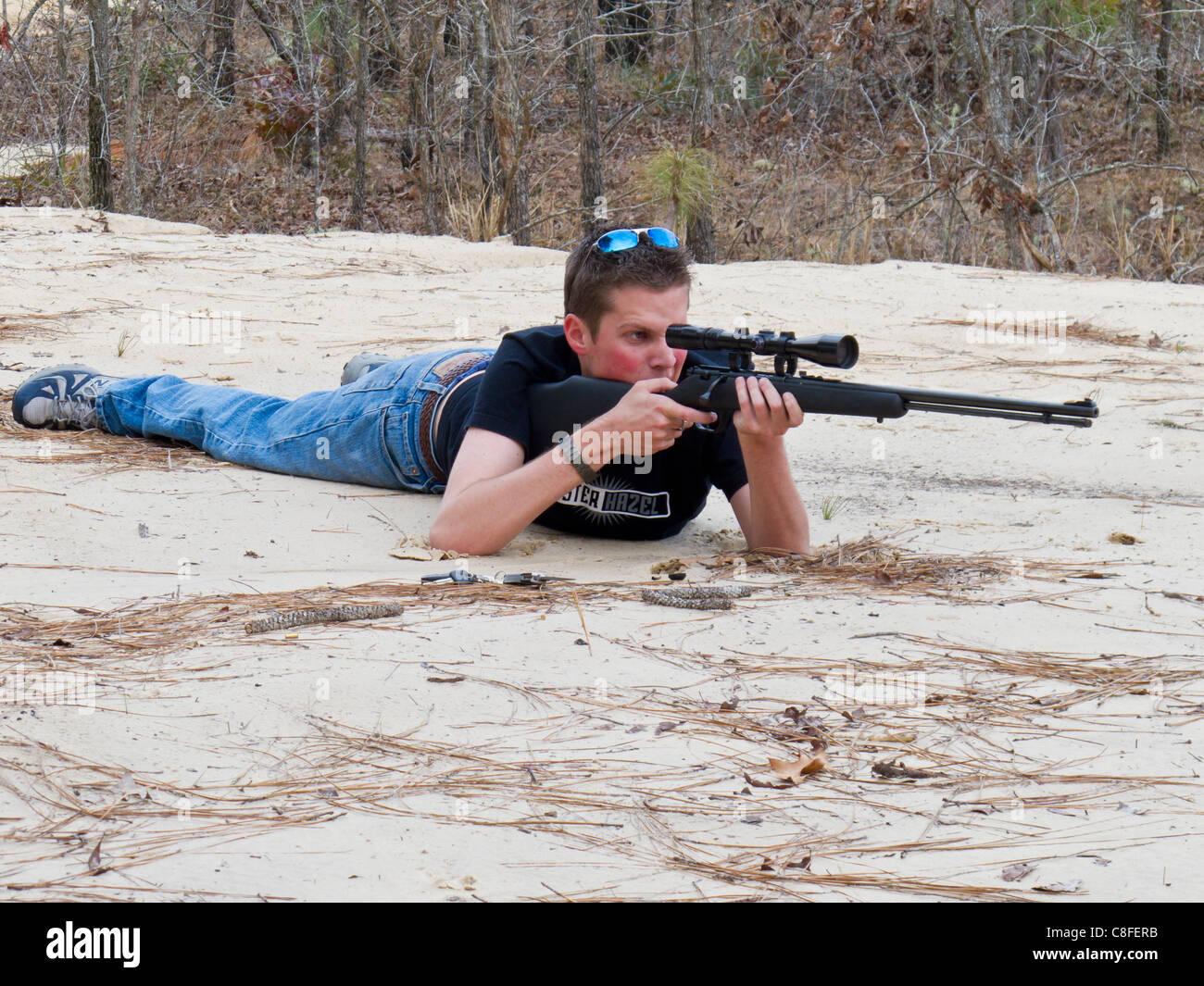 Teen male lying on ground shooting .22 caliber rifle with scope in Ocala, Florida, USA - Stock Image