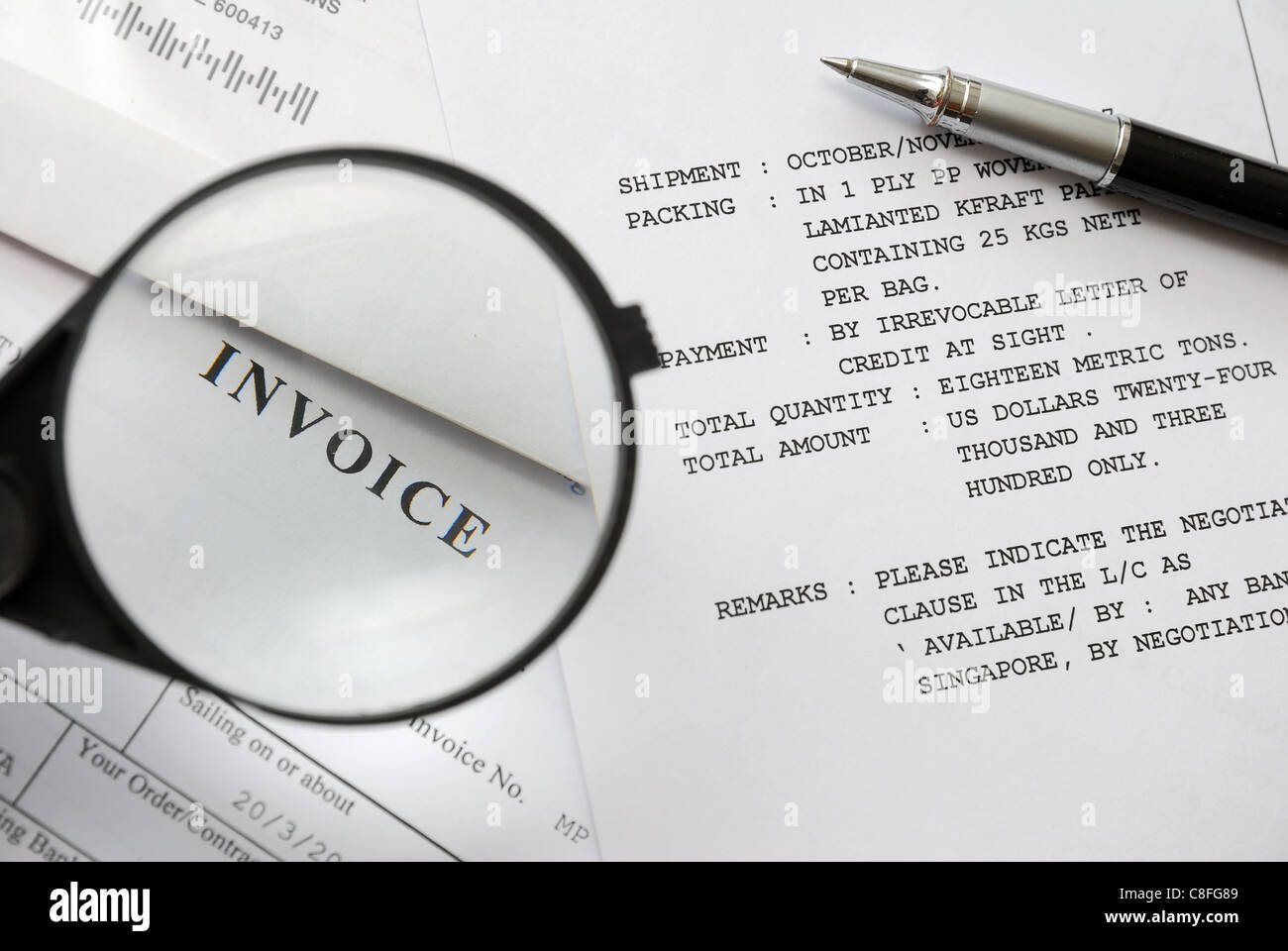 Magnifying glass on invoice word, signifying business and trading concepts. - Stock Image