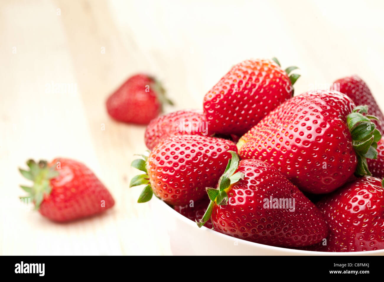 Appetizing strawberry in the bowl. Isolated on a white background. - Stock Image
