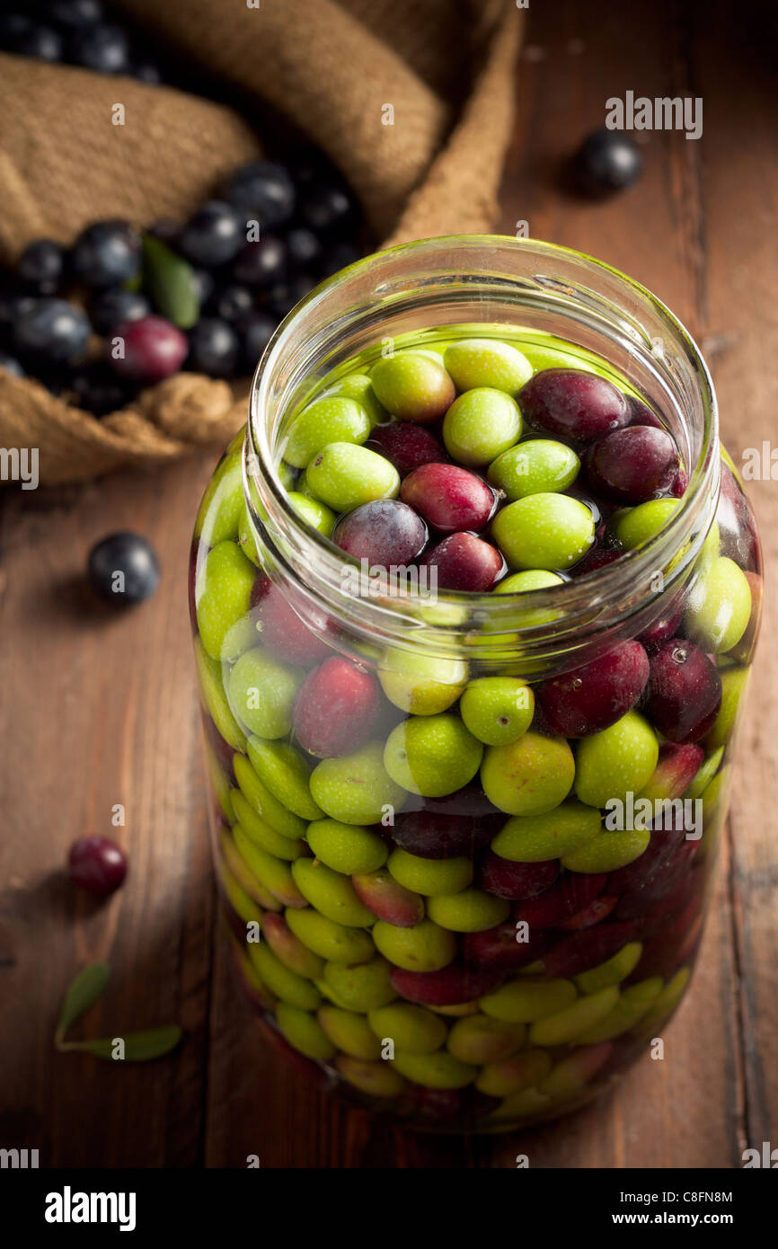 Olives in Brine (with Water and Salt in Glass Jar) on Wood - Stock Image