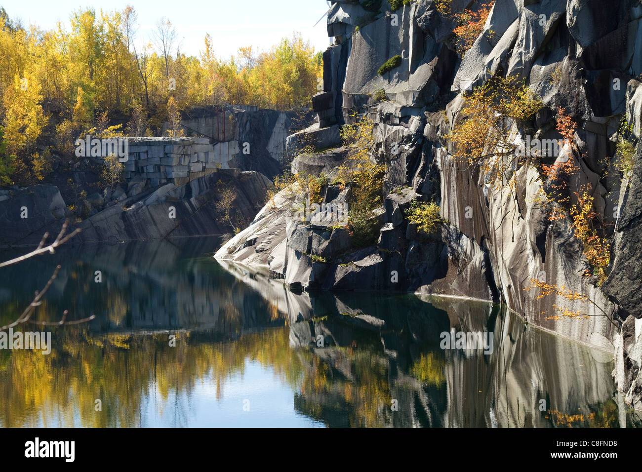 Quarry landscape of Granite rock, stone, at abandoned quarry in Barre, Vermont with autumn, fall, foliage colors. - Stock Image