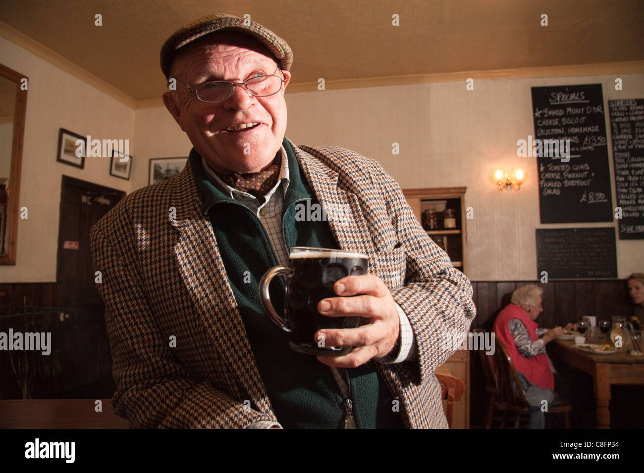 Suffolk raconteur, comedian and author Charlie Haylock having a pint of mild in a country pub. - Stock Image