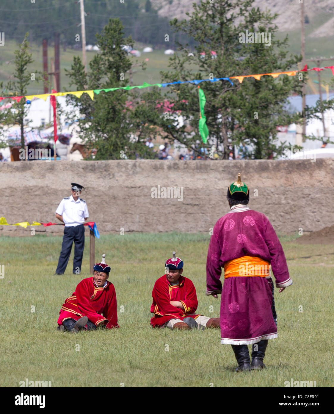 Wearing traditional dress an officials at the wrestling tournament watch the combat at the Tsetserleg Naadam. - Stock Image