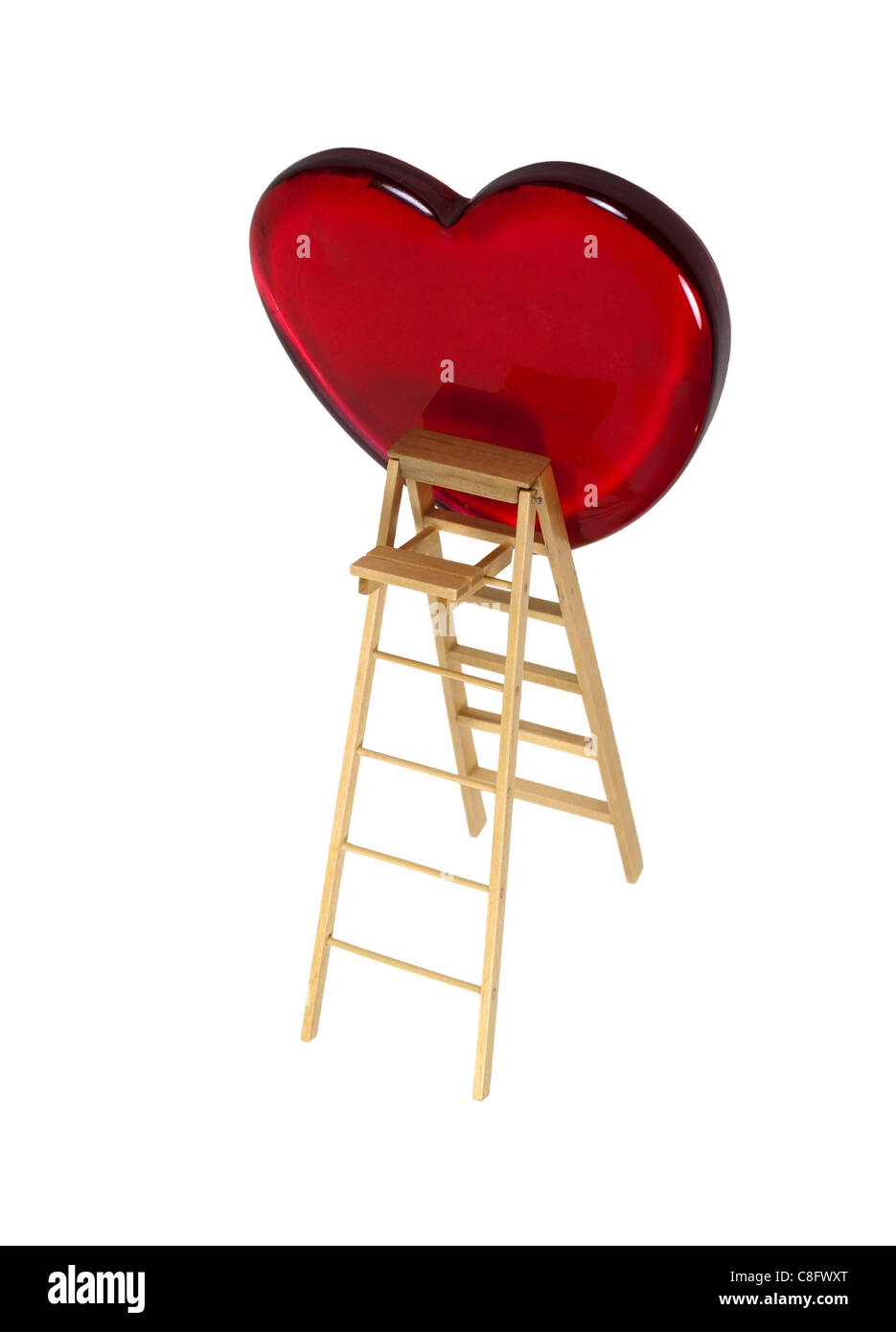 Love is an upward climb shown by a ladder leaning on a red heart - path included - Stock Image