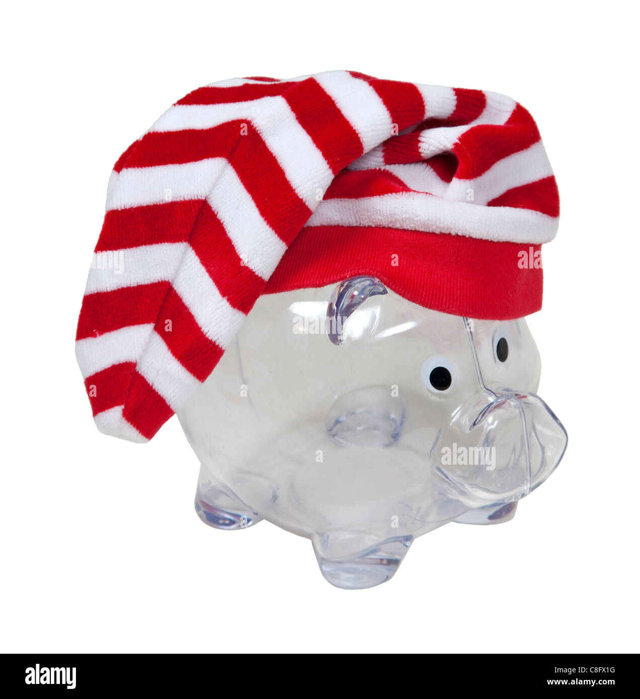 Traditional red and white Santa helper hat on a piggy bank for holiday funds - path included - Stock Image