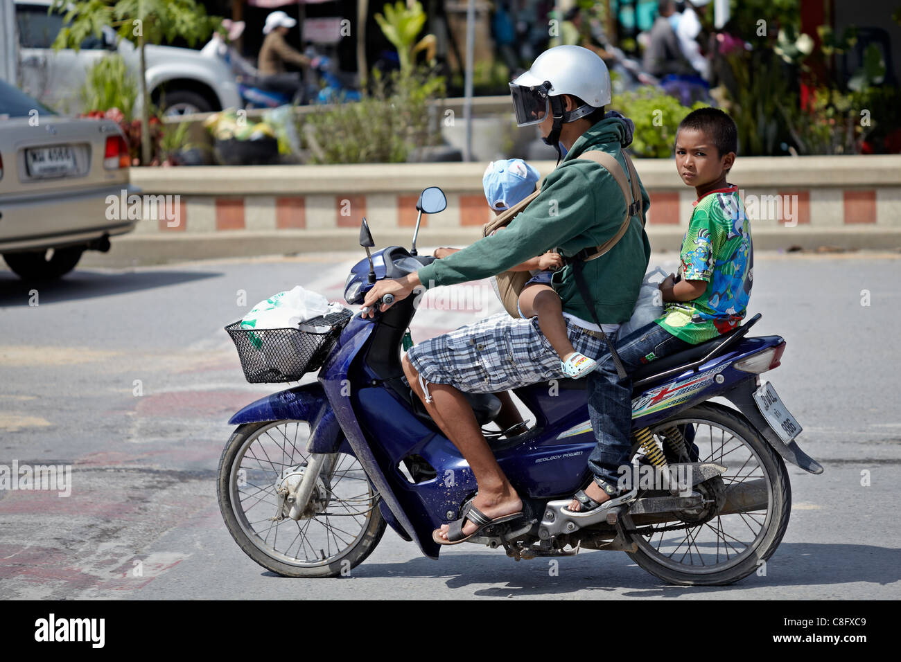 Mother precariously carrying her children on a motorcycle. She is wearing a crash helmet but the children are not. - Stock Image