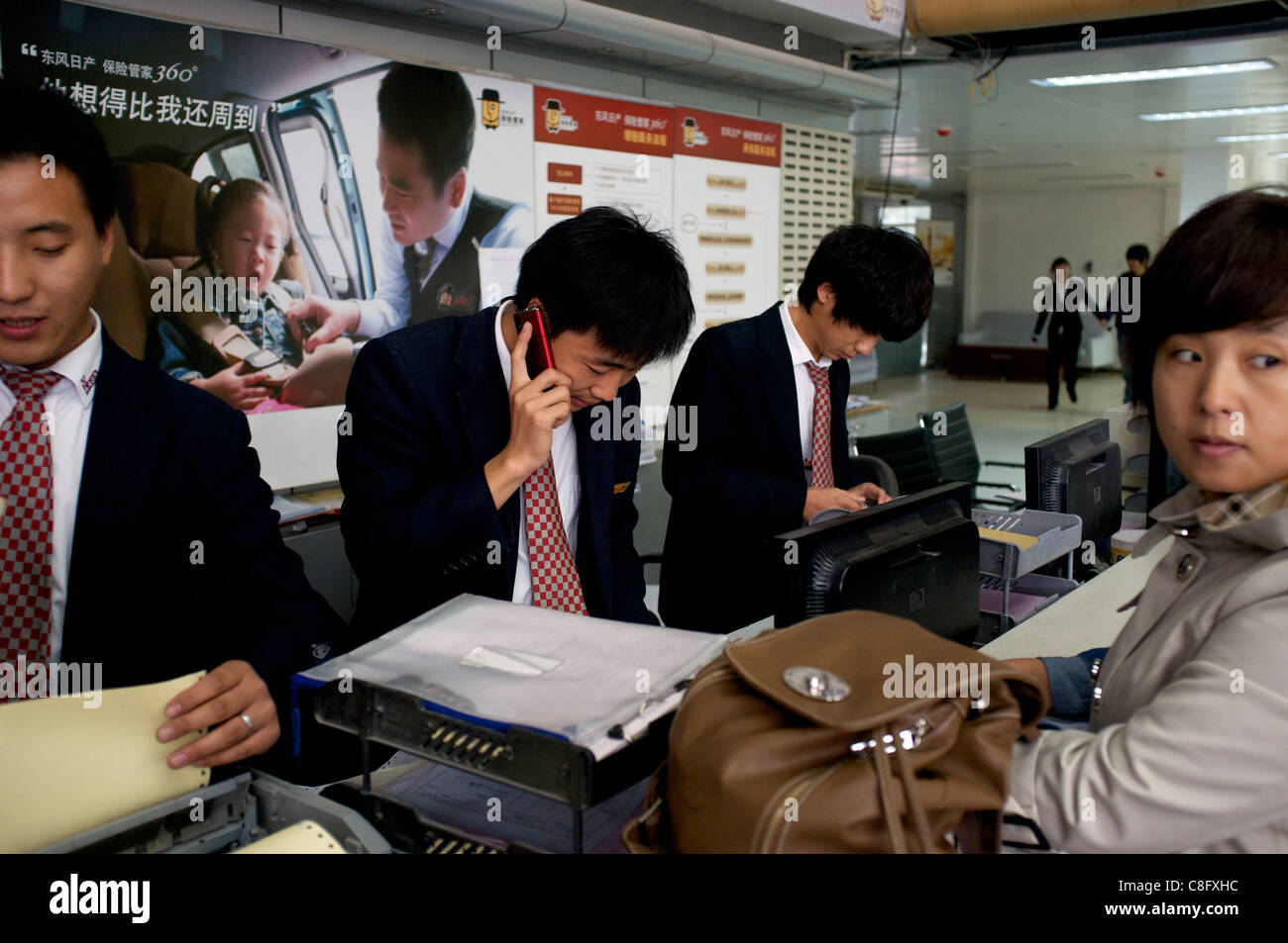 Chinese commercial vehicle insurance agents serve clients in Beijing, China. 22-Oct-2011 - Stock Image