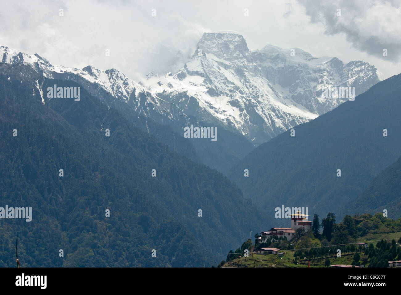 Gasa dzong in foreground with snow covered mountain range in background - Stock Image