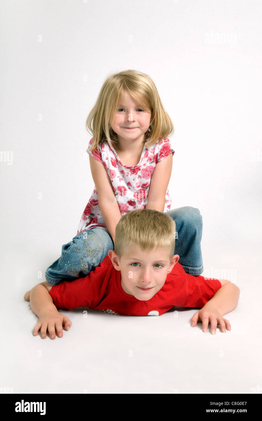 Two Caucasian children having fun with 7 year old girl sitting on top of 8 year old brother - Stock Image