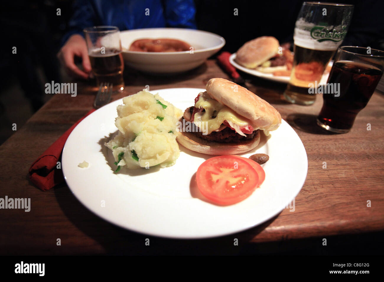 A cheeseburger served with champ (mashed potatoes with scallions) is served with beer in a pub. - Stock Image