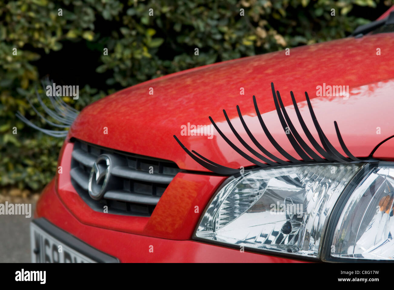 Amusing shot of a red car with eyelash accessory kit added taken in Bristol, UK.  This image can only be used for - Stock Image