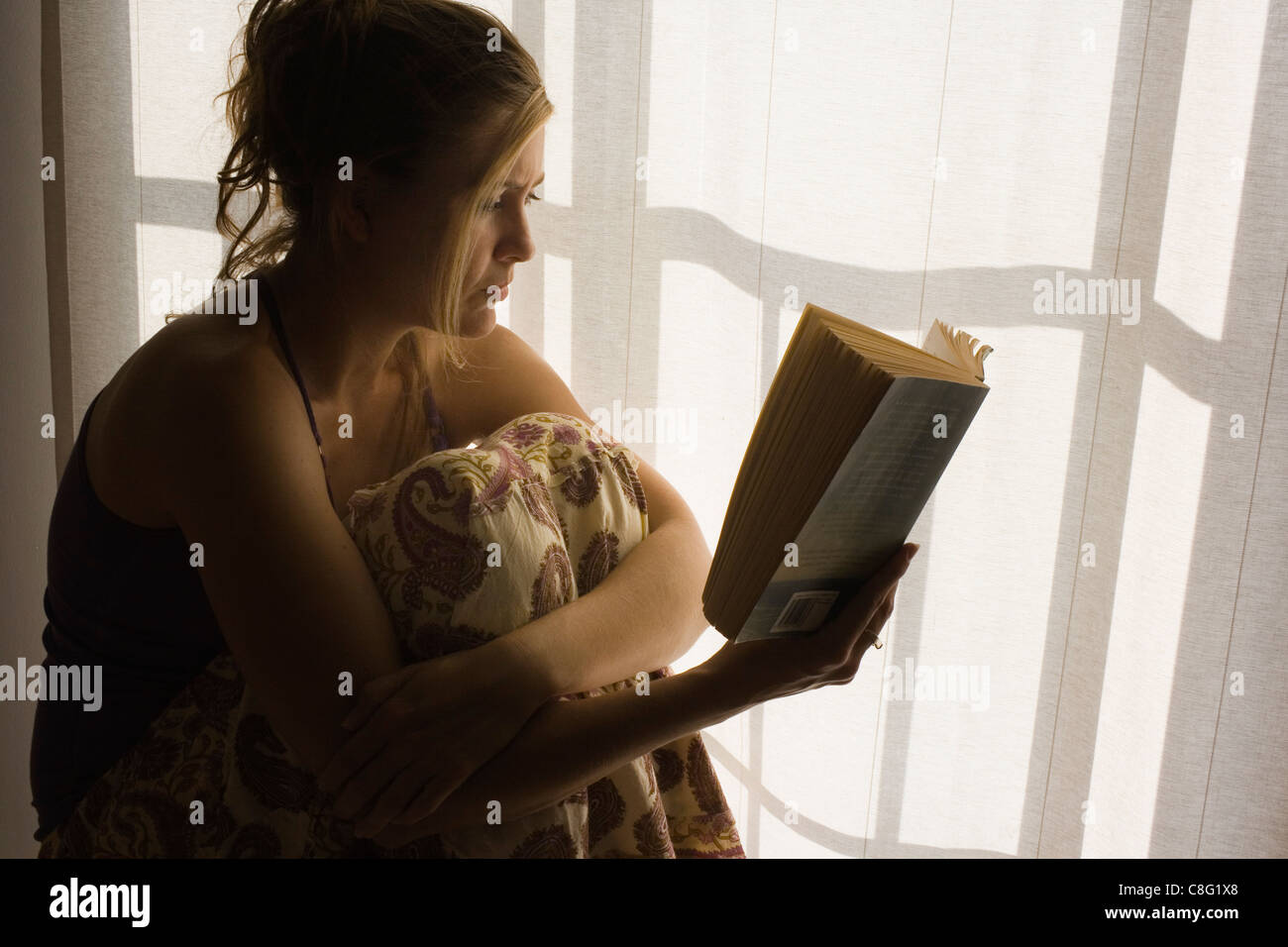 Young woman reading book - Stock Image
