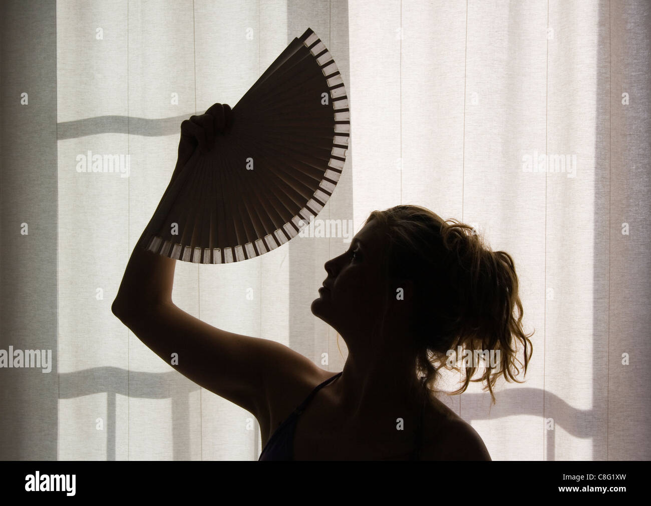 Silhouette of young woman with fan. - Stock Image