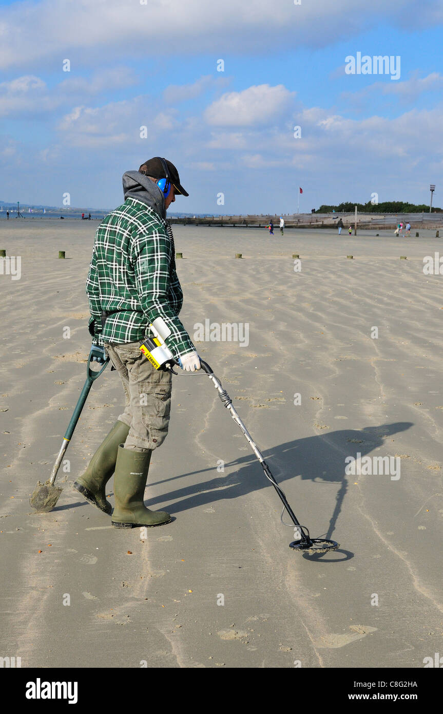 Man with metal detector  looking for lost valuables  on West Wittering beach  after the weekends crowds have departed - Stock Image