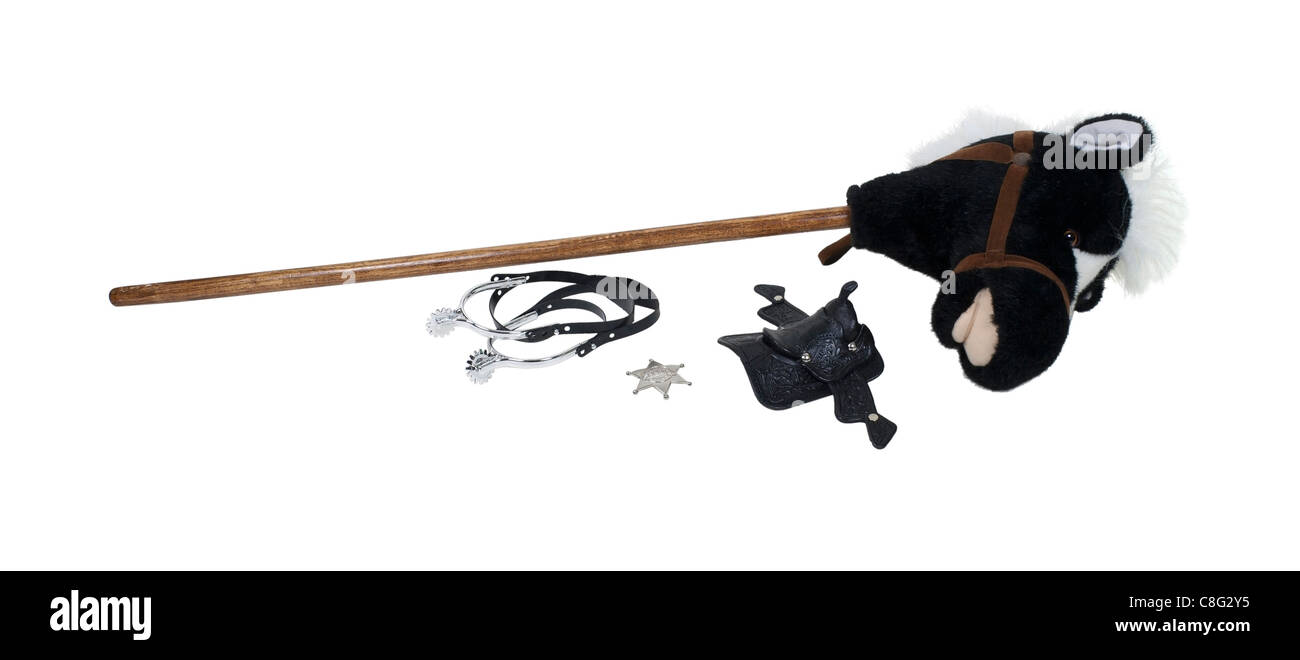 Child cowboy kit including spurs, sheriff star, saddle and a hobby horse - path included - Stock Image