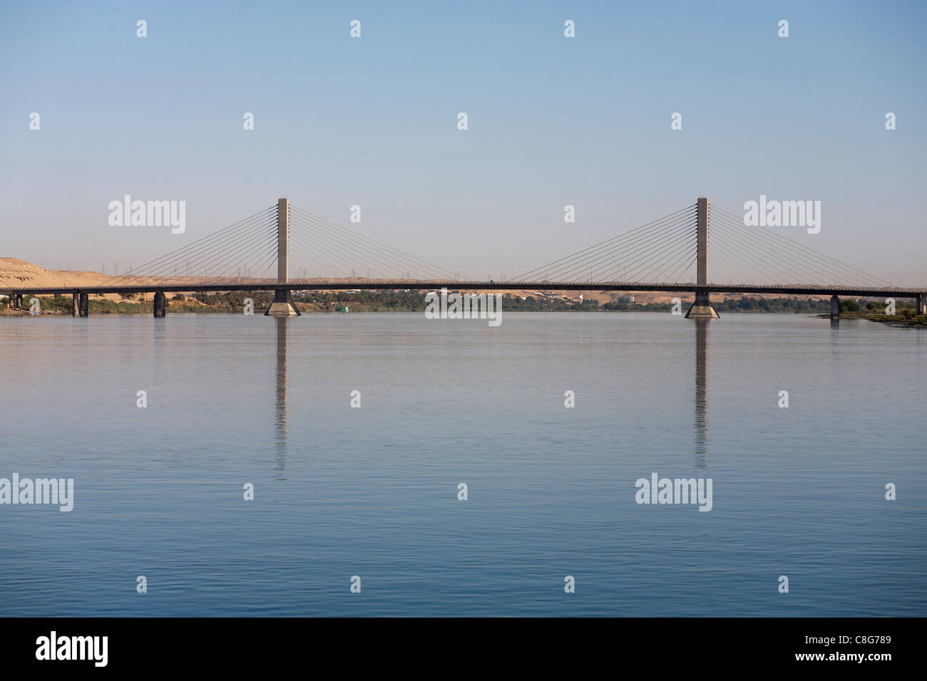 Long shot of the Aswan suspension bridge resembling a flat boat with two sails  spanning the river Nile, Egypt - Stock Image