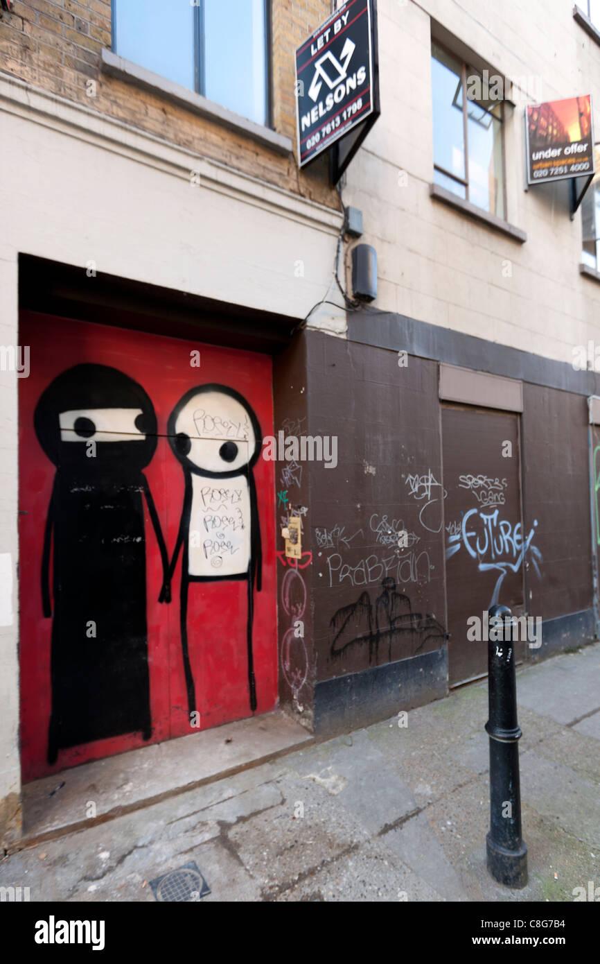 Stik figures painted in a doorway, Princelet Street, Spitalfields, London, UK. - Stock Image