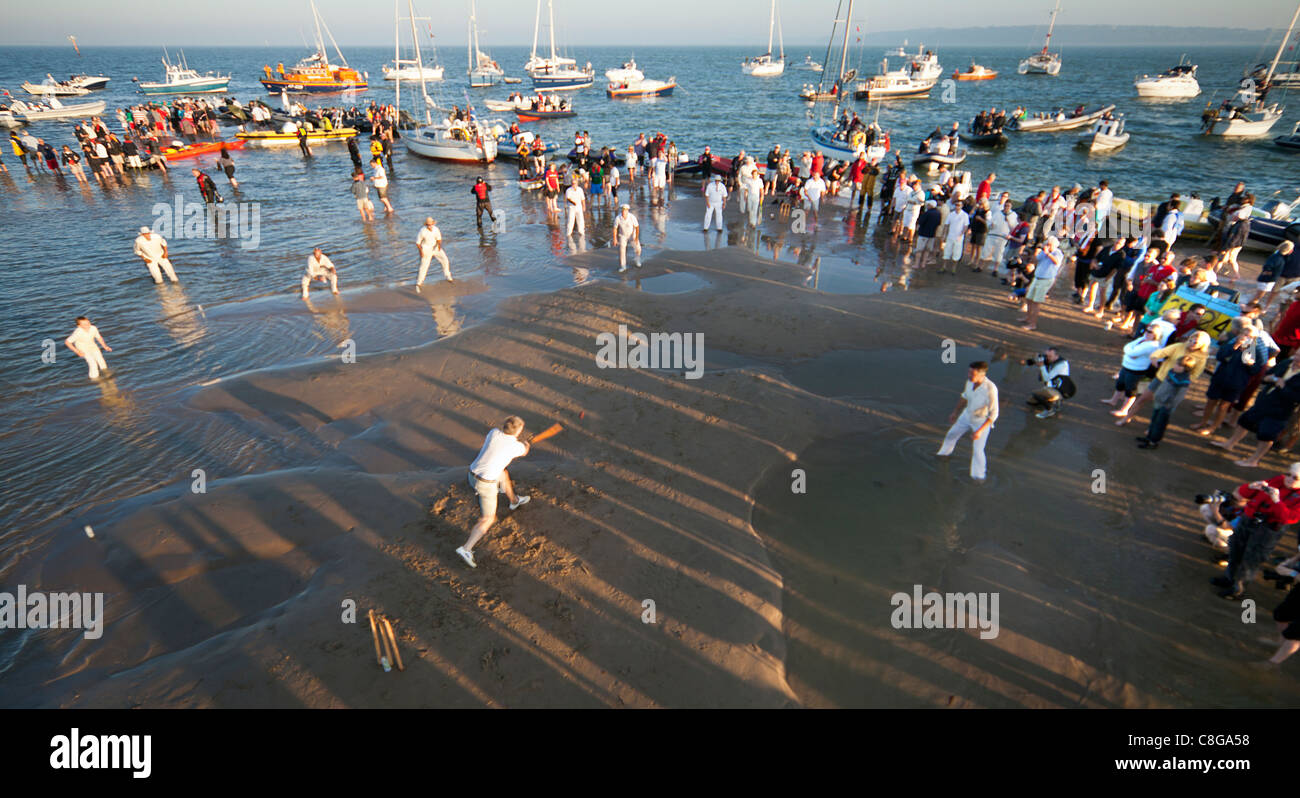 Brambles Cricket English Eccentric Match played in the middle of a sandbank in the Solent at spring low tide for - Stock Image