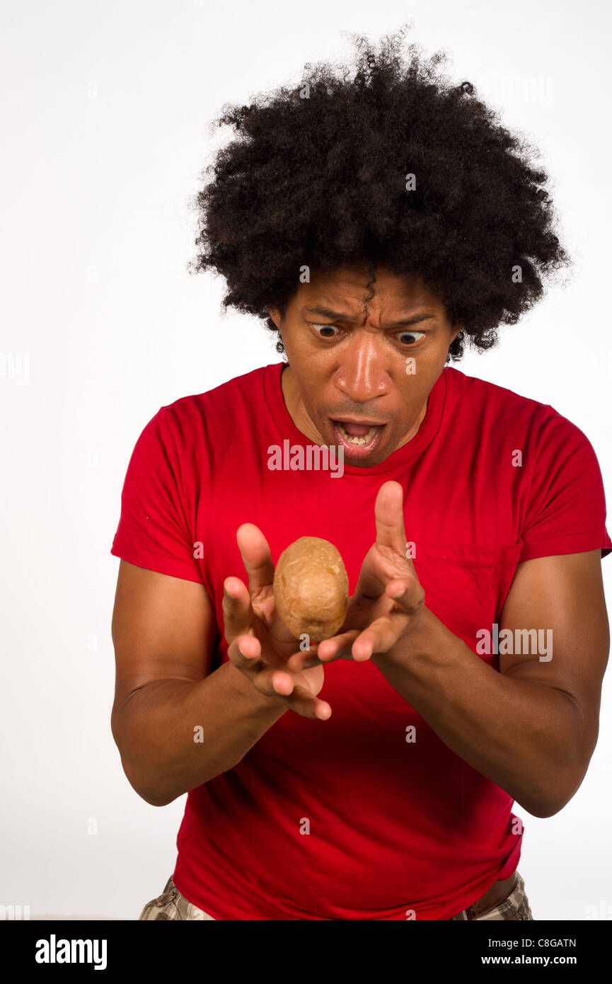 Guy juggling with a hot potato, not sure what to do with it - Stock Image