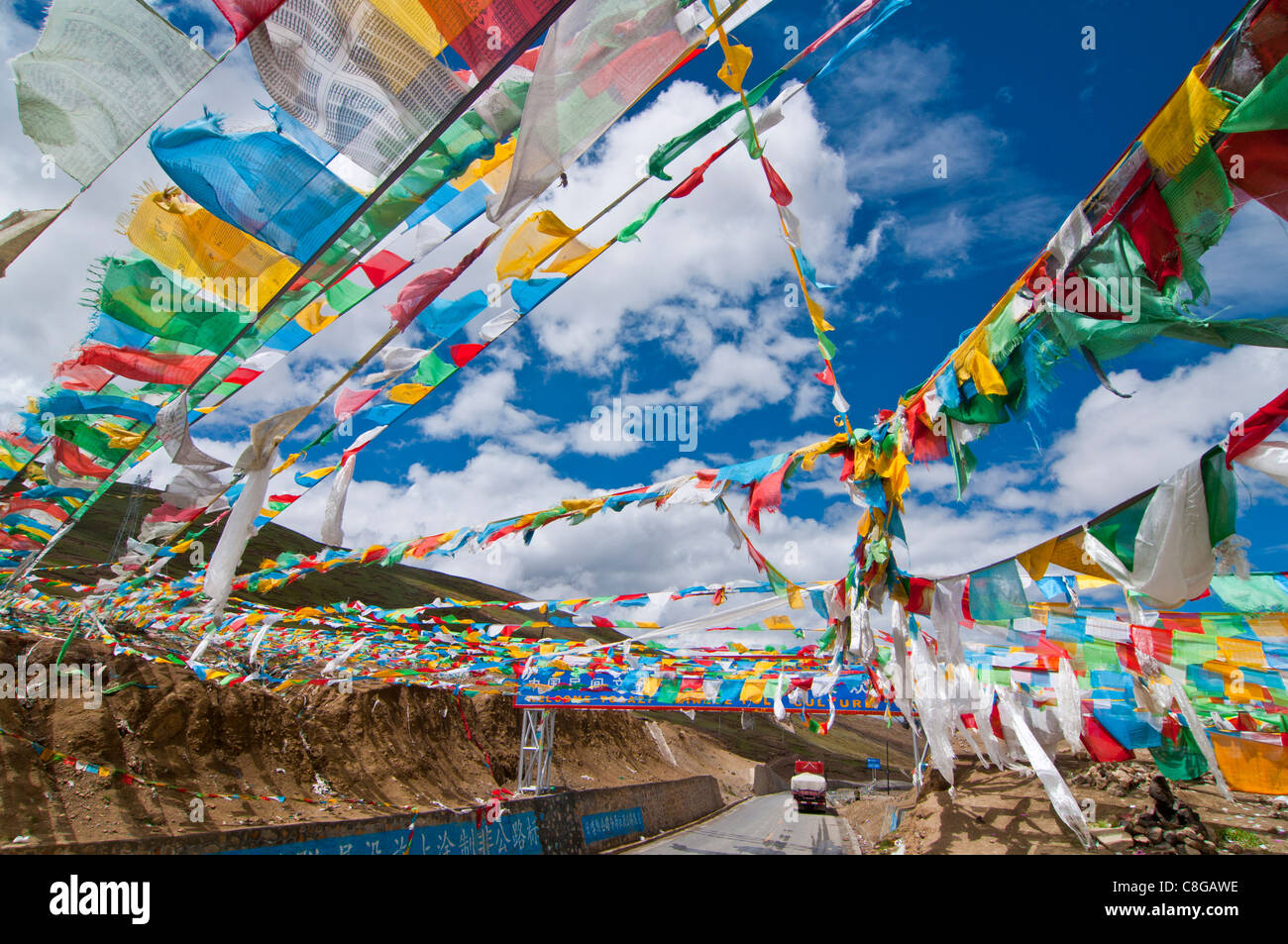 Prayer flags crossing the Friendship Highway between Lhasa and Kathmandu, Tibet, China - Stock Image