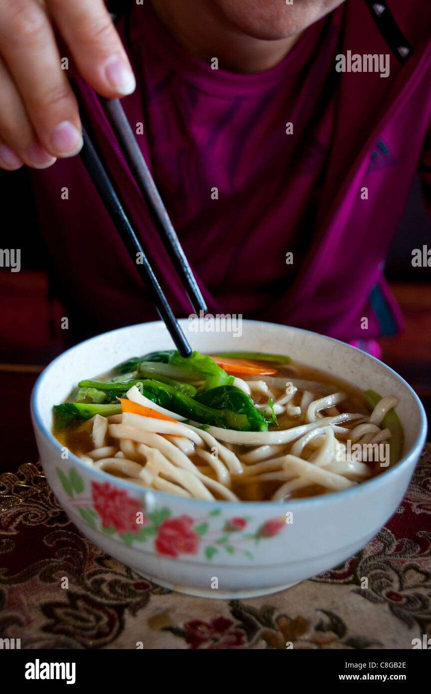 Woman eating noodle soup, Lhasa, Tibet, China - Stock Image