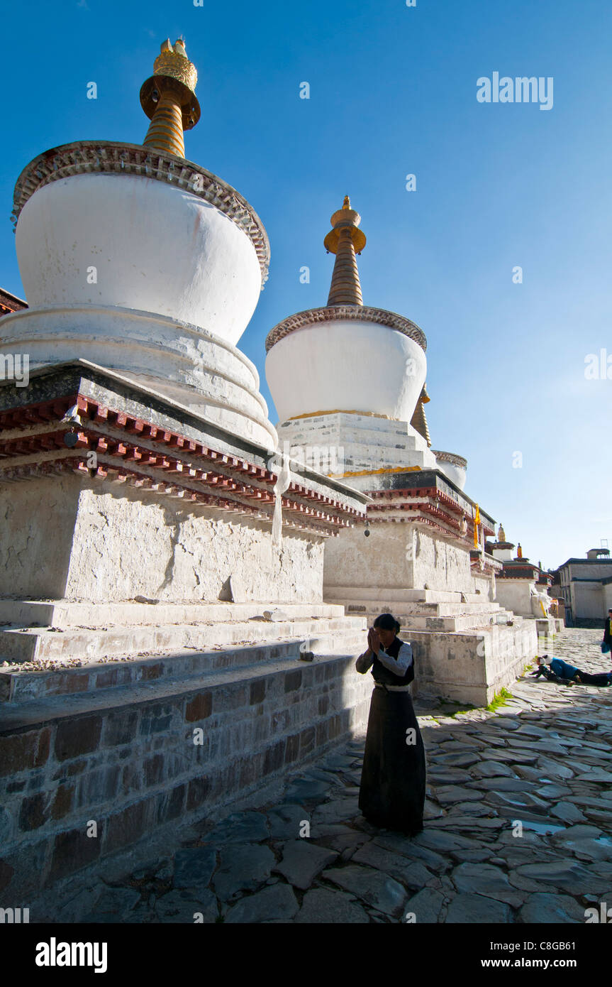 Pilgrim in front of the white stupas at the Tashilumpo monastery, Shigatse, Tibet Autonomous Region, China - Stock Image