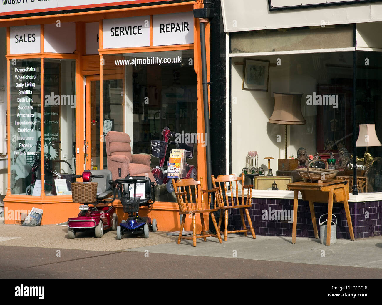 small shops selling mobility scooters useful equipment and used furniture - Stock Image